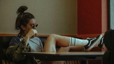 meisje met zonnebril op die met haar benen gekruist zit, sneaker trends 2018