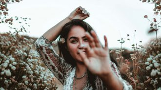vrouw in veld met lange wimpers die wimperkruller gebruikt